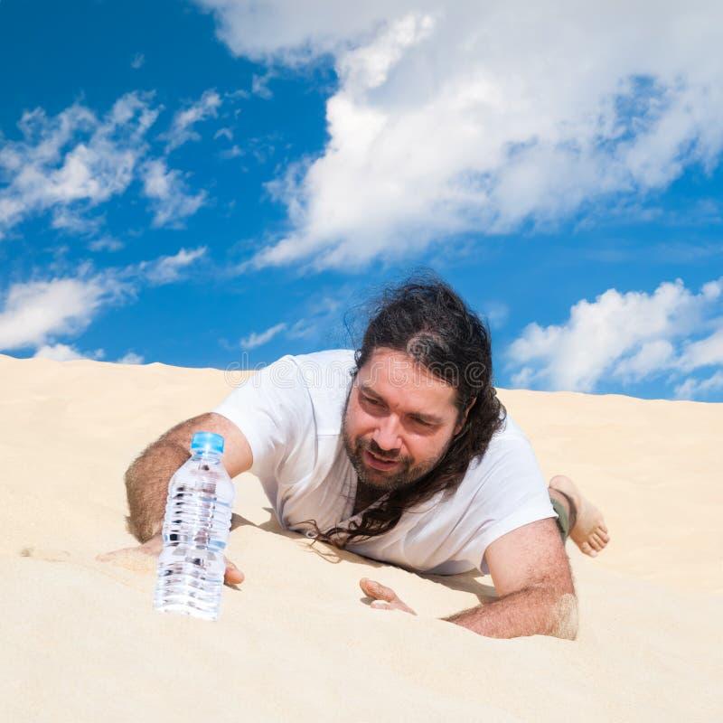 El hombre sediento en el desierto alcanza para el agua foto de archivo libre de regalías