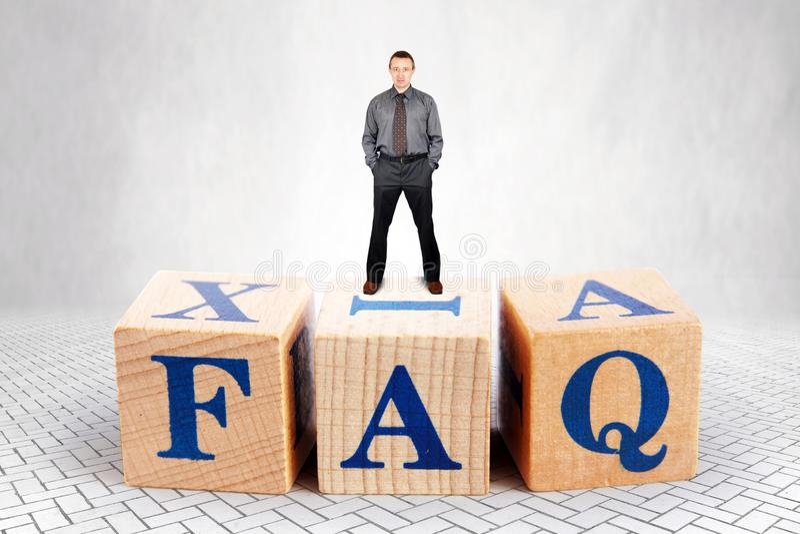El hombre seguro de sí mismo se coloca en el top del montón de bloques de madera con el FAQ de las letras fotos de archivo libres de regalías
