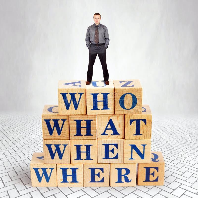 El hombre seguro de sí mismo se coloca en el top del montón de bloques de madera con las preguntas que lo que cuándo dónde imagen de archivo