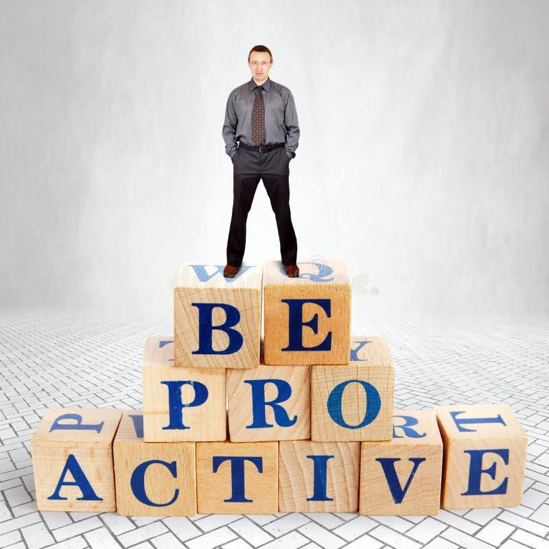 El hombre seguro de sí mismo se coloca en el top del montón de bloques de madera con una llamada sea dinámico fotografía de archivo libre de regalías