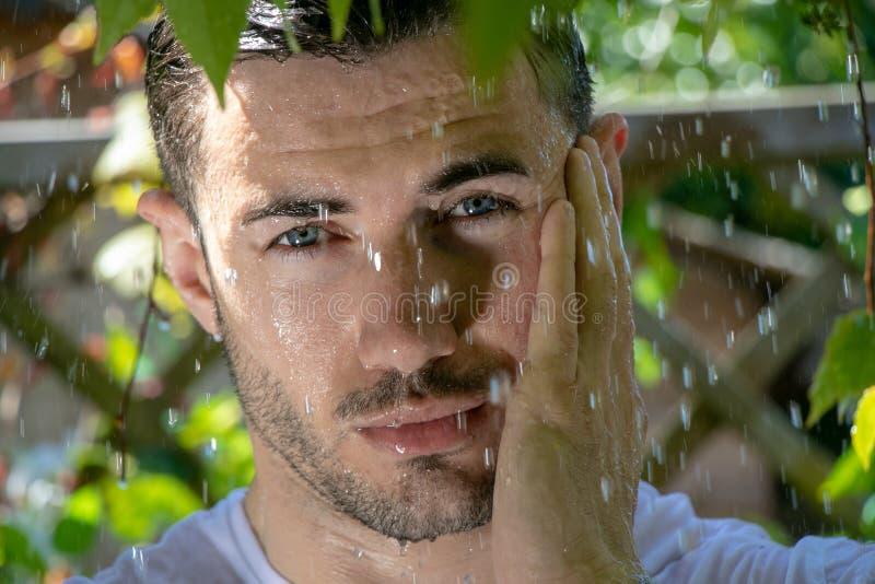 El hombre semi desnudo hermoso con los músculos y el pecho desnudo cogió en la ducha de la lluvia en jardín fotografía de archivo libre de regalías
