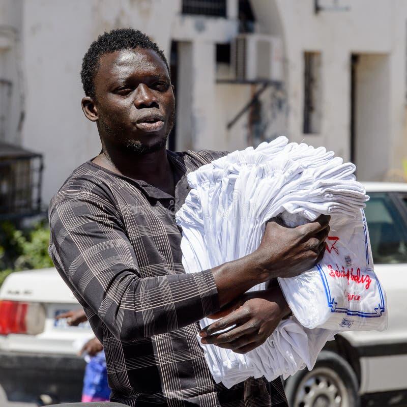 El hombre senegalés no identificado camina a lo largo de la calle con las mercancías f imagen de archivo