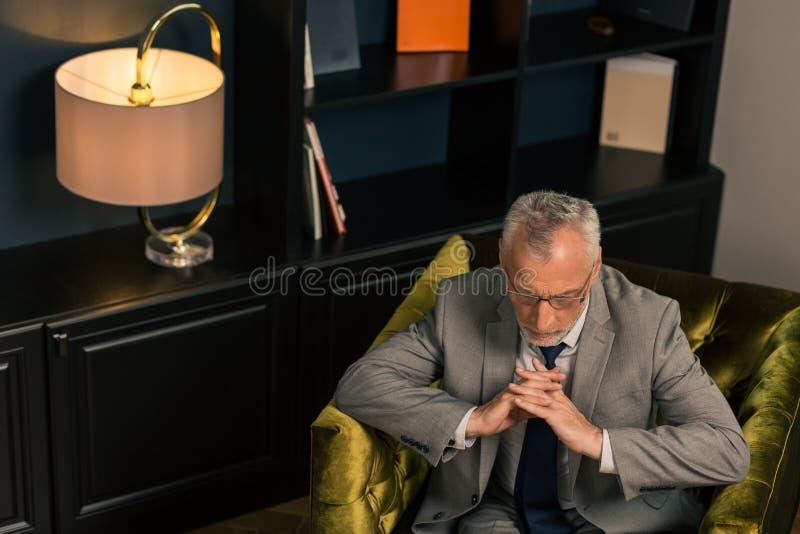 El hombre serio pensativo que se sentaba con sus fingeres cruzó imagen de archivo libre de regalías