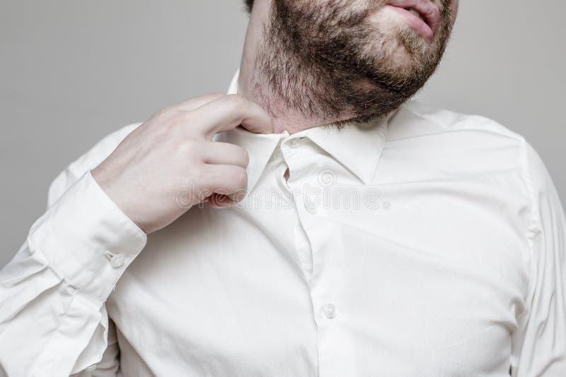 El hombre sin afeitar en la camisa blanca es apretado y sofocante fotos de archivo libres de regalías