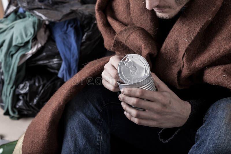El hombre sin hogar come una comida imagen de archivo