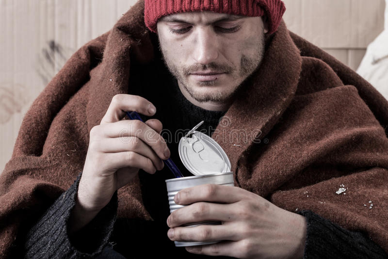 El hombre sin hogar congelado come fotos de archivo
