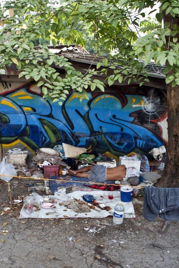 El hombre sin hogar duerme en una calle de Bangkok fotografía de archivo libre de regalías