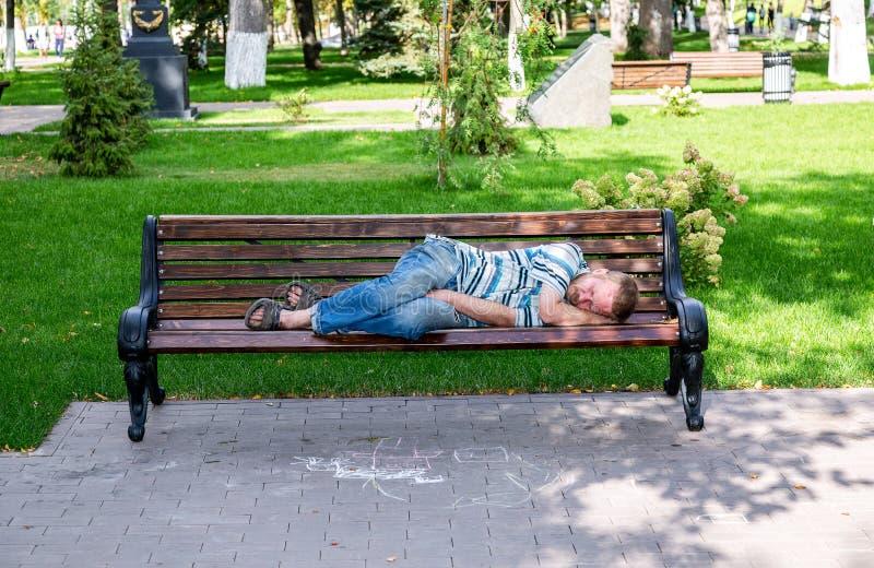 El hombre sin hogar está durmiendo en el banco en el parque foto de archivo libre de regalías