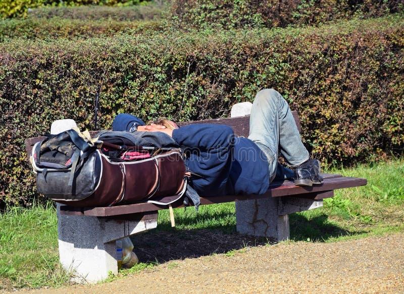 El hombre sin hogar está durmiendo en un banco fotos de archivo libres de regalías