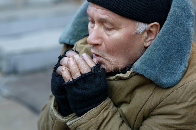 El hombre sin hogar está sintiendo frío fotografía de archivo