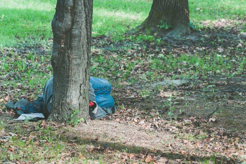 El hombre sin hogar pobre del refugiado duerme por motivo del parque en la ciudad foto de archivo libre de regalías