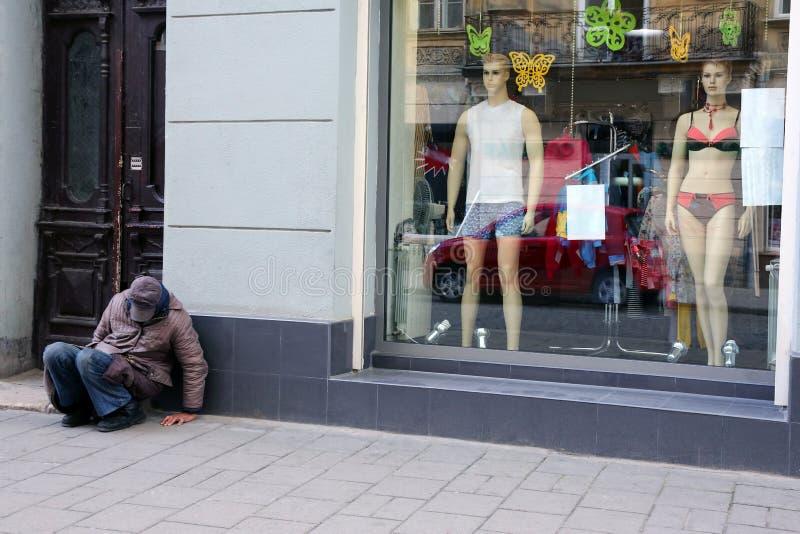 El hombre sin hogar se sienta cerca de la ventana de la tienda fotos de archivo libres de regalías