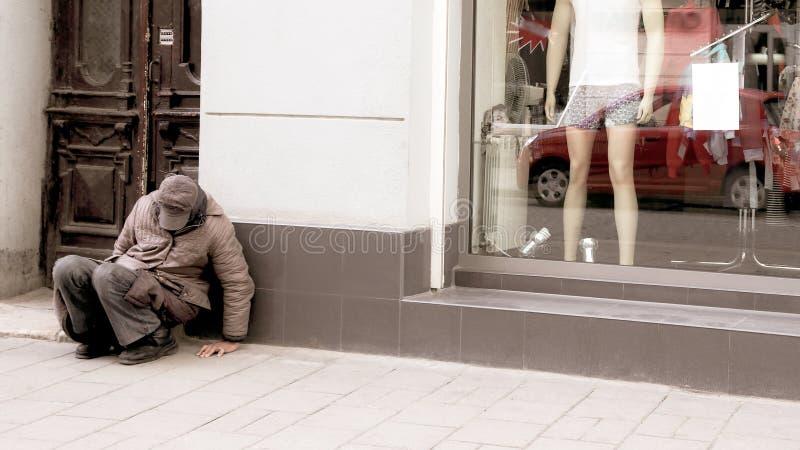 El hombre sin hogar se sienta cerca de la ventana de la tienda imagen de archivo