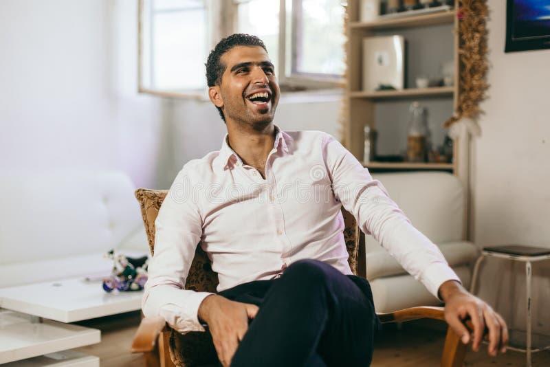 El hombre sirio confiado y alegre está escuchando una conversación fotos de archivo