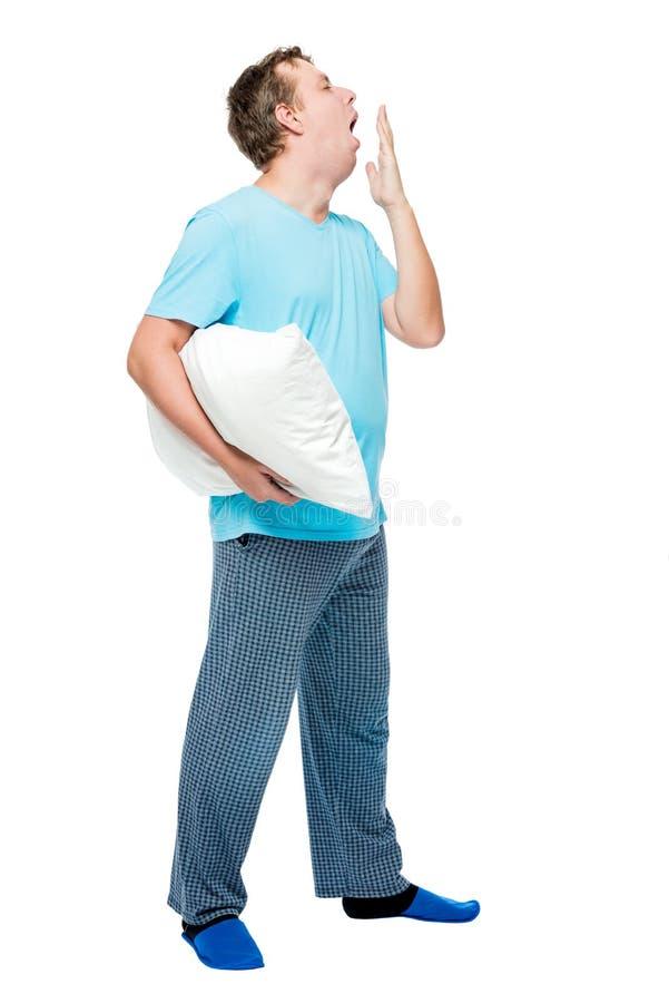 El hombre soñoliento en pijamas bosteza, retrato en integral en blanco imágenes de archivo libres de regalías