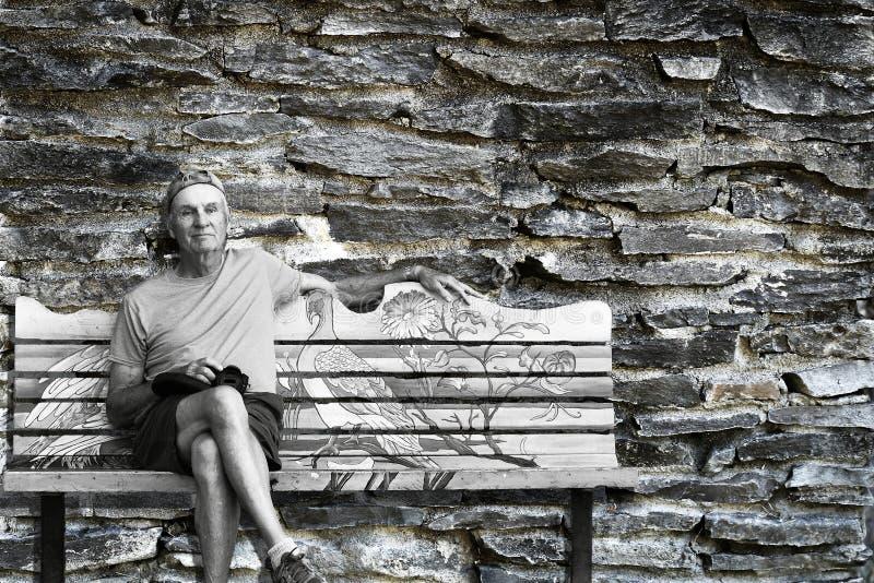 El hombre solo mayor se sienta en banco con la pared de ladrillo de piedra sucia vieja en el fondo fotos de archivo libres de regalías