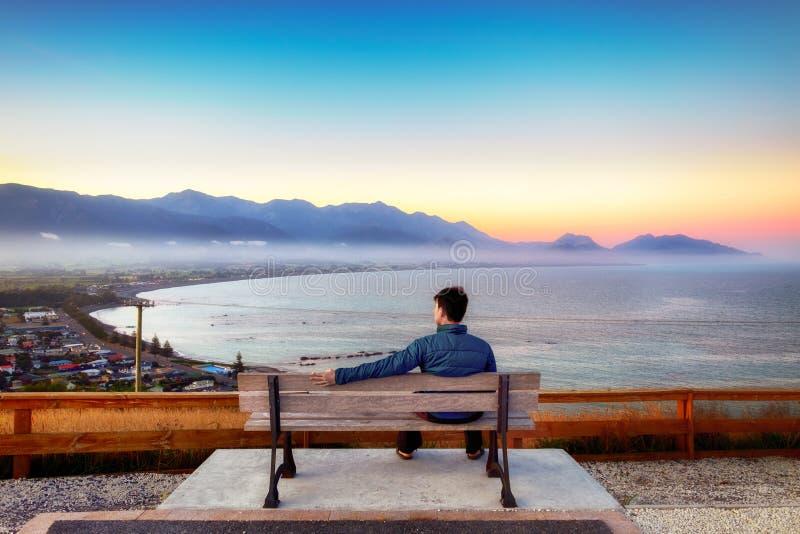 El hombre solo se sienta en un banco en una colina en Kaikoura, Nueva Zelanda fotografía de archivo