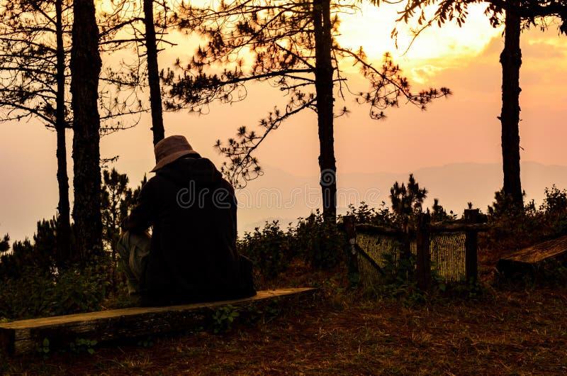 El hombre solo y triste tiene sentarse en el de madera con tiempo de la puesta del sol encendido foto de archivo libre de regalías