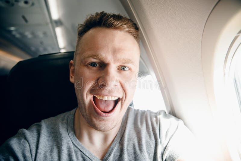 El hombre sonríe y toma la foto del selfie en los aviones planos concepto del recorrido fotos de archivo libres de regalías
