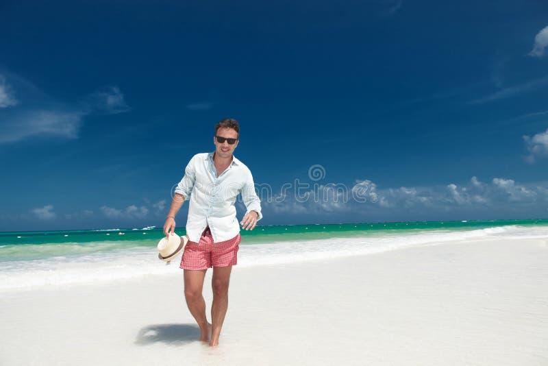 El hombre sonriente camina en la playa con el sombrero a disposición imagenes de archivo