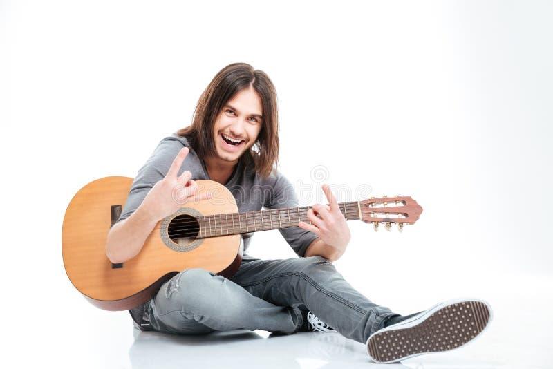 El hombre sonriente con la guitarra que sienta y que hace la roca gesticula imagen de archivo libre de regalías