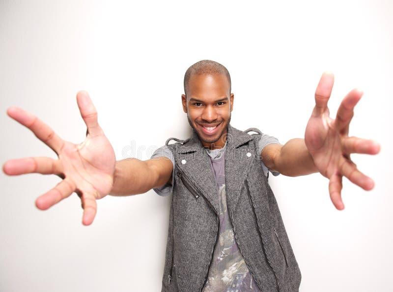 El hombre sonriente con los brazos extendidos y las manos se abre foto de archivo
