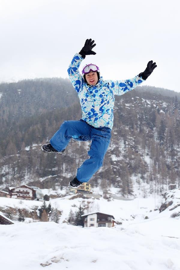 El hombre sonriente en juego del deporte del esquí salta en la montaña imagen de archivo