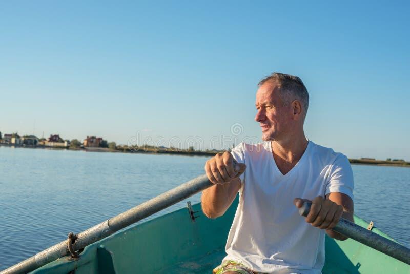 El hombre sonriente está remando en un bote pequeño en un mar tranquilo fotografía de archivo