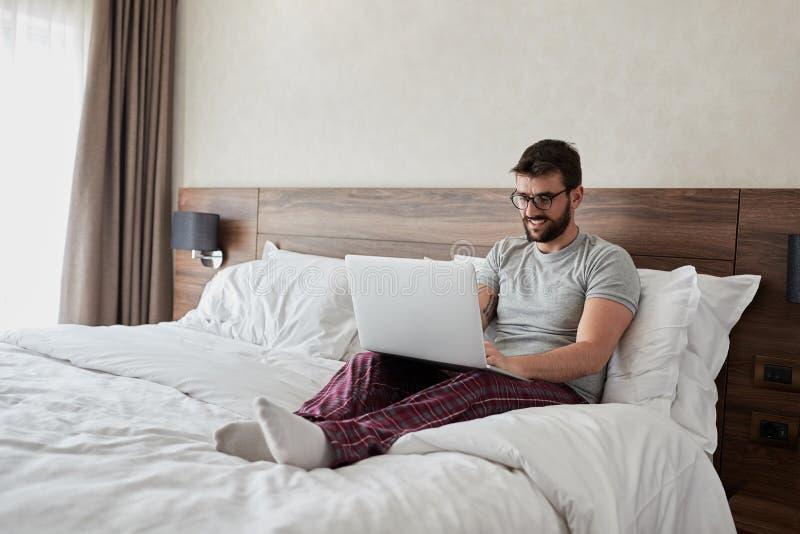 El hombre sonriente está trabajando con el ordenador portátil, mintiendo en cama imagenes de archivo