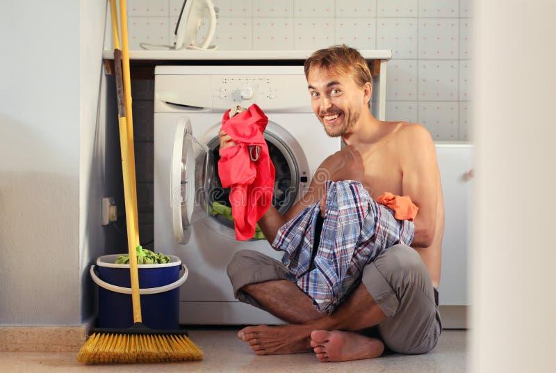 El hombre sonriente hermoso feliz carga el lavadero en la lavadora Quehacer dom?stico del soltero, concepto masculino del ama de  foto de archivo libre de regalías