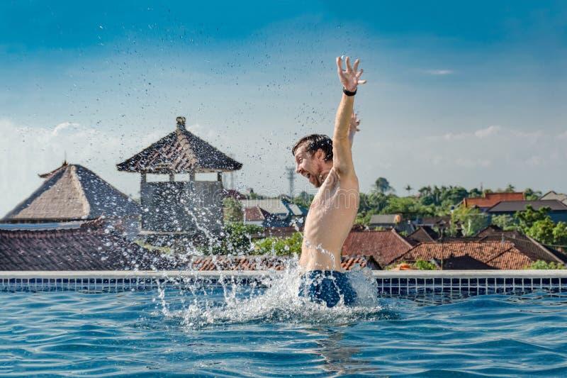 El hombre sonriente joven muy feliz, delgado, el saltar del agua de la piscina con salpica, en el tejado, y las manos para arriba foto de archivo