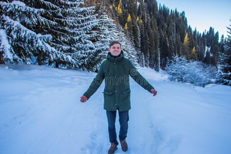 El hombre sonriente se divierte en las montañas nevosas imágenes de archivo libres de regalías