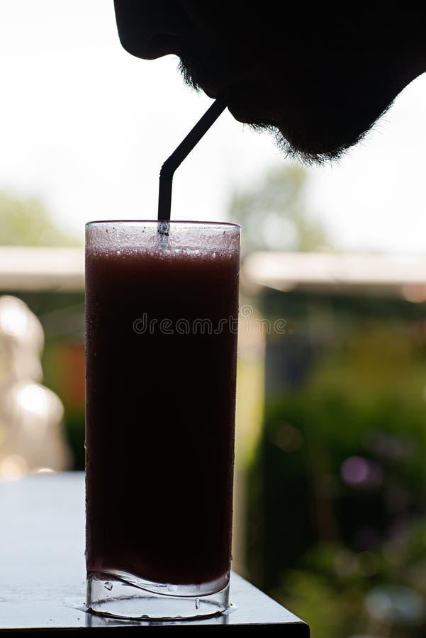 El hombre sorbe la bebida congelada, silueta imagenes de archivo
