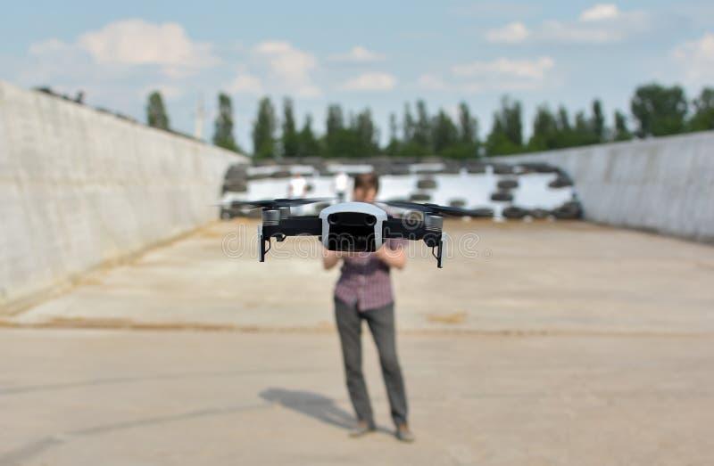 El hombre sostiene el control remoto con sus manos mientras que el helicóptero está volando en fondo El abejón asoma detrás del p fotografía de archivo libre de regalías