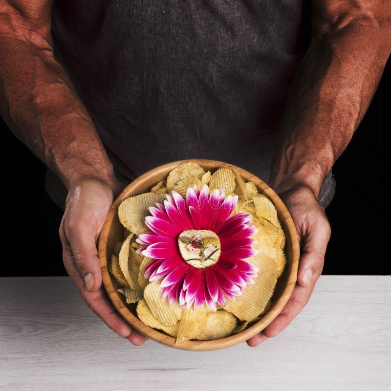 El hombre sostiene el cuenco con las patatas fritas fotografía de archivo libre de regalías