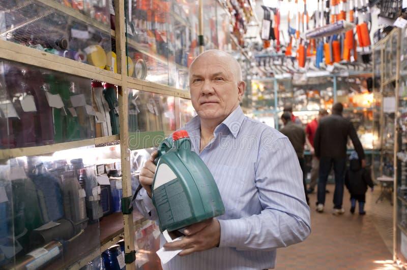 El hombre sostiene el petróleo de motor en almacén de las piezas de automóvil fotos de archivo
