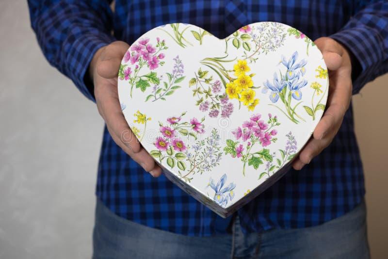 El hombre sostiene hacia fuera un regalo en una caja en la forma de un corazón con el flover imagenes de archivo