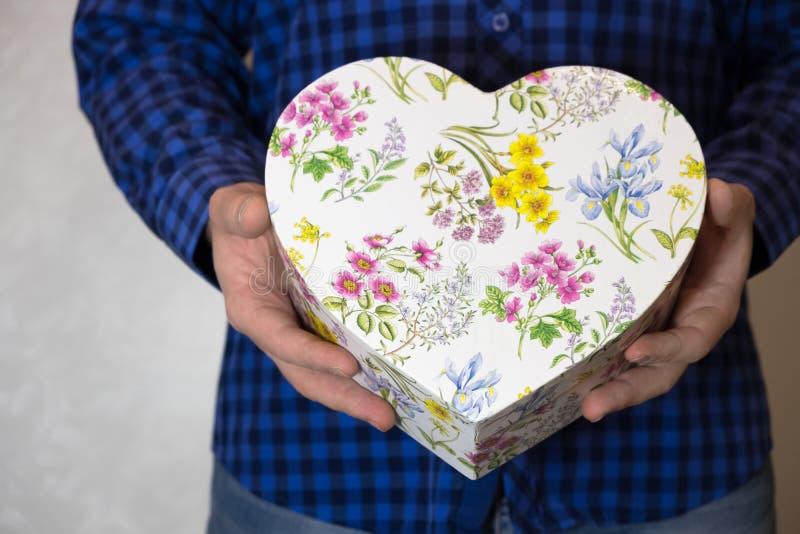 El hombre sostiene hacia fuera un regalo en una caja en la forma de un corazón con el flover imágenes de archivo libres de regalías