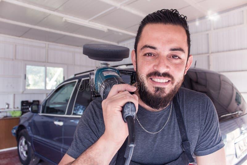 El hombre sostiene la herramienta de pulido del coche en las manos y la sonrisa foto de archivo