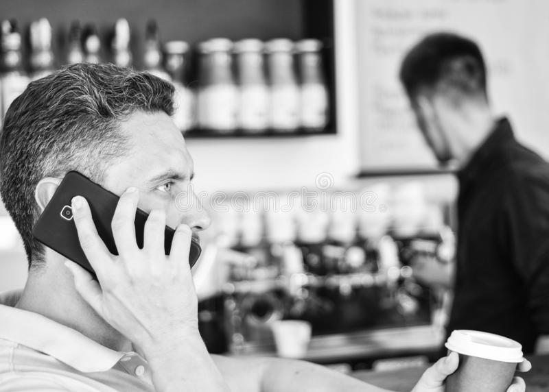 El hombre sostiene la taza de bebida mientras que tenga conversaci?n m?vil Caf? a ir opci?n ?til para la gente ocupada Amigo de l imagen de archivo