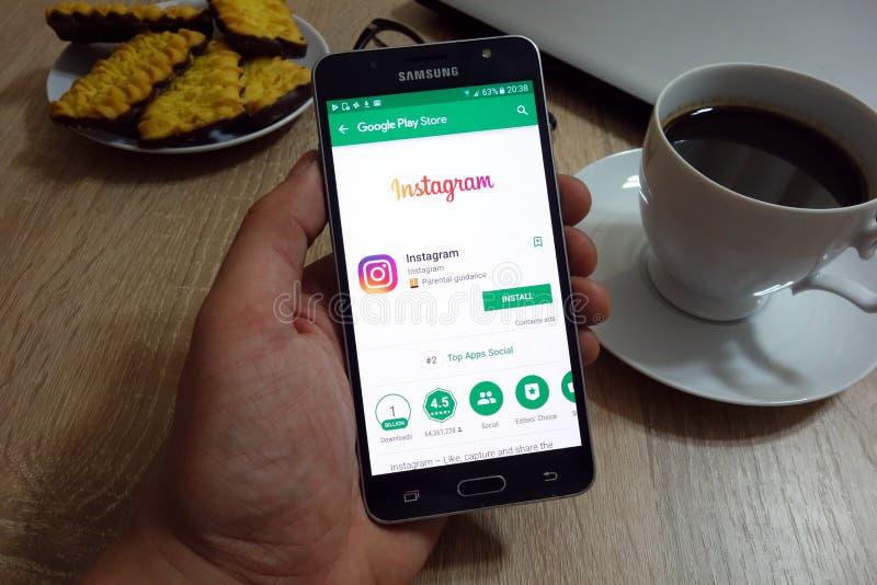 El hombre sostiene el smartphone de Samsung con el app de Instagram en página web del Google Play Store en la pantalla foto de archivo libre de regalías