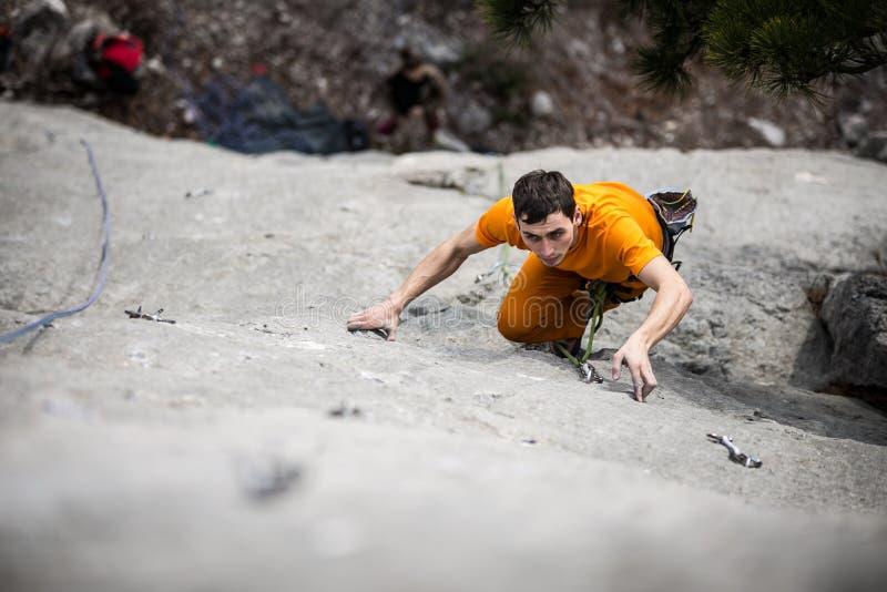 El hombre sube una roca fotos de archivo