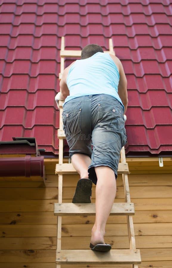 El hombre subió las escaleras para comprobar el tejado de la casa después del huracán imágenes de archivo libres de regalías