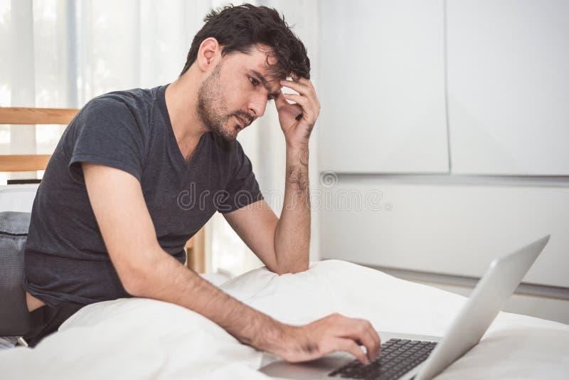 El hombre subrayó hacia fuera de trabajo con el ordenador portátil en dormitorio Tecnología foto de archivo