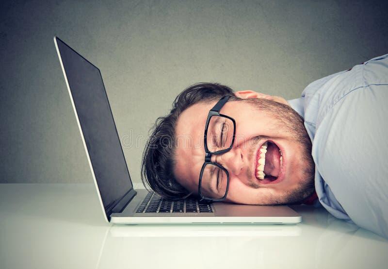 El hombre subrayado del empleado que se sentaba en el escritorio con la cabeza en la sensación del ordenador portátil trabajó dem fotos de archivo