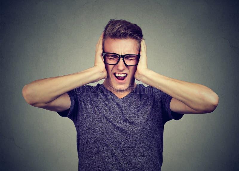El hombre subrayado frustrado puede el ` t tolerar ruido más fuerte fotografía de archivo