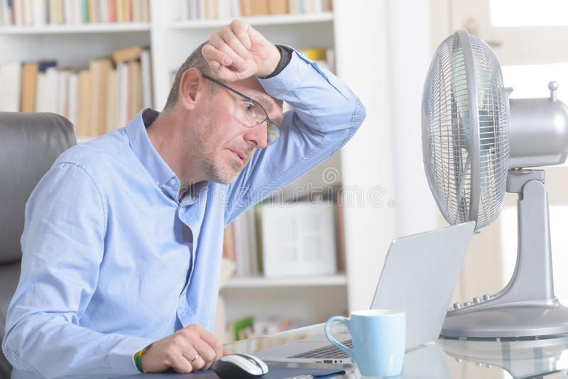 El hombre sufre de calor en la oficina o en casa foto de archivo