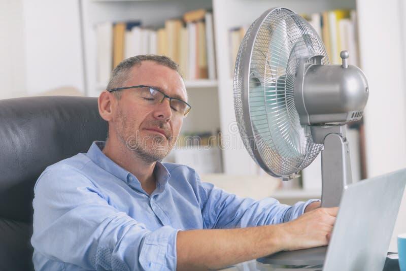 El hombre sufre de calor en la oficina o en casa imagenes de archivo