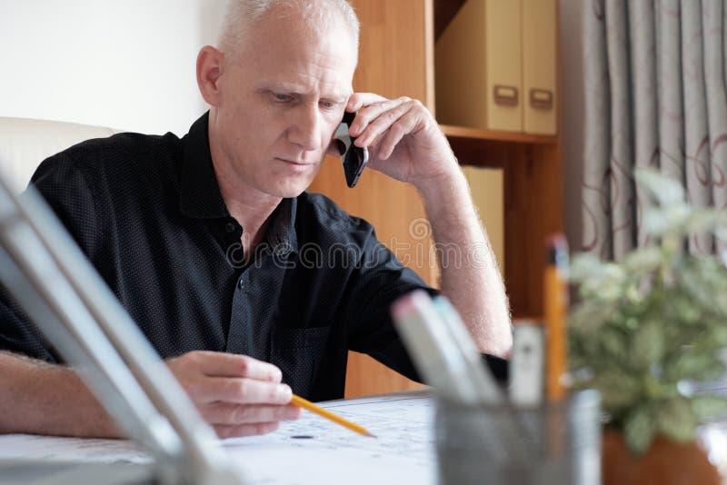 El hombre tiene charla ocupada sobre el teléfono foto de archivo