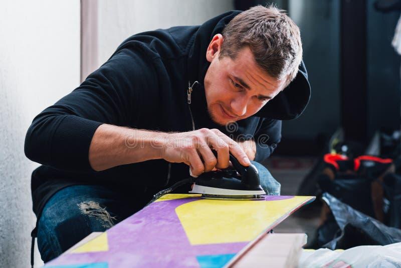El hombre tiene cuidado encerando la snowboard foto de archivo libre de regalías